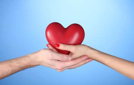 bondad: El hombre y la mujer con el corazón rojo en las manos sobre fondo azul