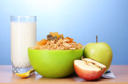 tasty cornflakes in green bowl, apples and glass of milk on wooden table on blue background Stock Photo - 12231190