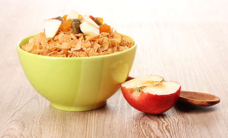 tasty cornflakes in bowl with dried fruits and apple on wooden table photo