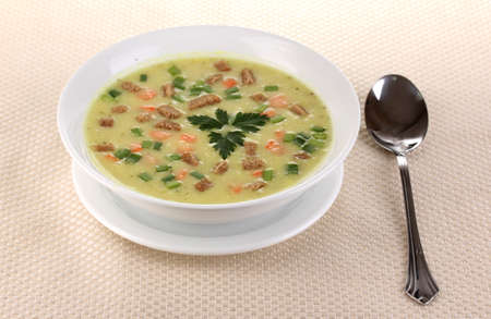 Tasty soup on beige tablecloth isolated on white photo