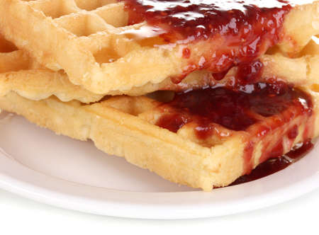 Tasty waffles with jam on plate close-up isolated on white photo