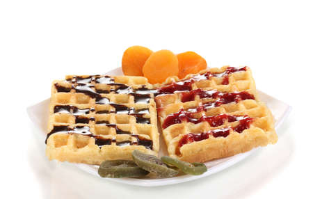 Sweet waffles with jam and chocolate on plate isolated on white photo