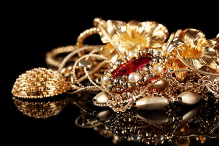 Various gold jewellery on black background Stock Photo - 12266594