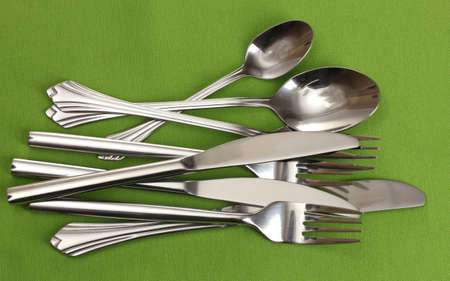 Forks, spoons and knives on a green tablecloth photo