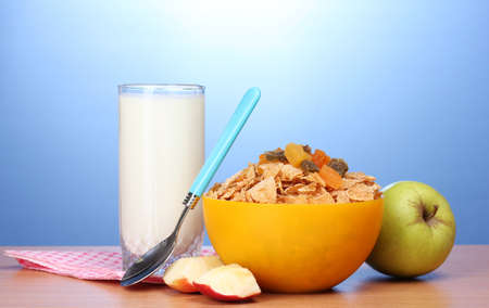 tasty cornflakes in yellow bowl, apples and glass of milk on wooden table on blue background photo