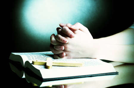 jesus word: Female hands on open russian holy bible on black backround Stock Photo