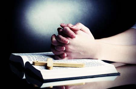 cruz religiosa: Manos femeninas en ruso Santa Biblia abierta en negro backround