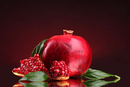 ripe pomegranate fruit with leaves on red background Stock Photo - 12266115