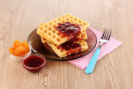 Tasty waffles with jam on plate on wooden background photo