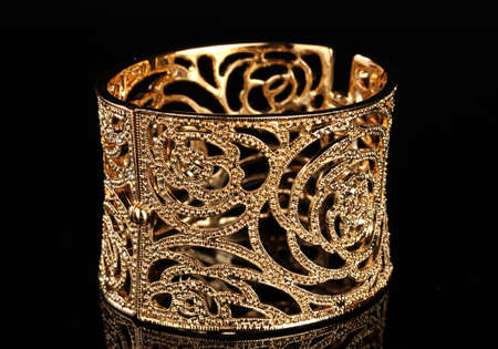beautiful golden bracelet on black background photo