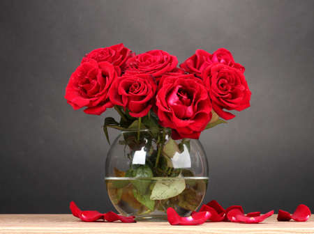 Beautiful red roses in vase on wooden table on gray background photo