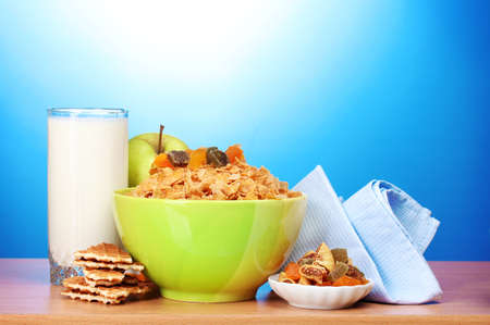 tasty cornflakes in green bowl, apples and glass of milk on wooden table on blue background Stock Photo - 12265827