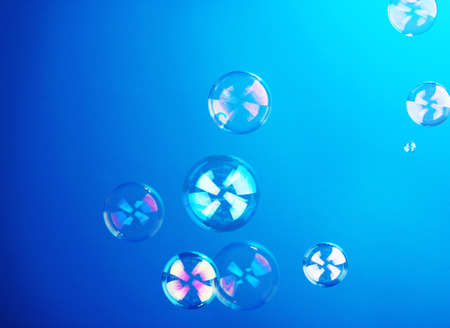 Soap bubble on blue background photo