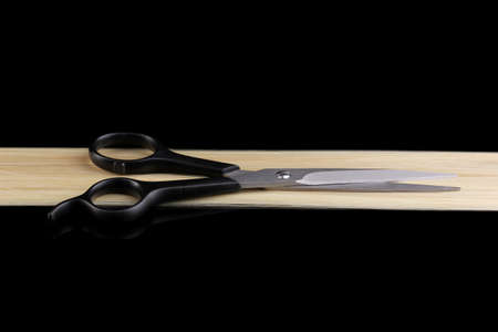 Shiny blond hair and hair cutting shears isolated on black photo