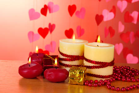 Beautiful candles with romantic decor on a wooden table on a red background Stock Photo - 12266044