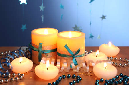 Beautiful candles, gifts and decor on wooden table on blue background Stock Photo - 12266040