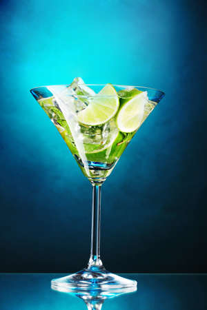 glass of cocktail with lime and mint on blue background photo