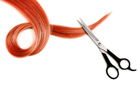 Shiny red hair and hair cutting shears isolated on white Фото со стока