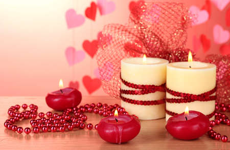 Beautiful candles with romantic decor on a wooden table on a red background Stock Photo - 12239339