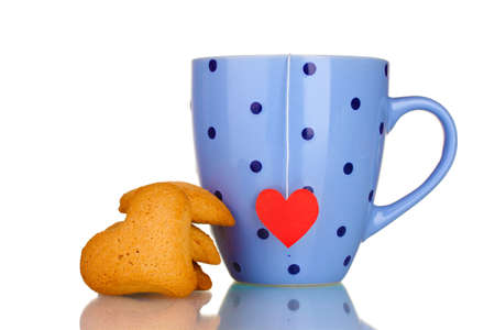 Blue cup with tea bag and heart-shaped cookies isolated on white photo