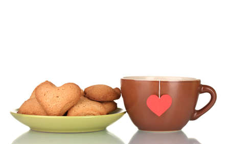 Brown cup with tea bag and heart-shaped cookies on green plate isolated on white Stock Photo - 12240596