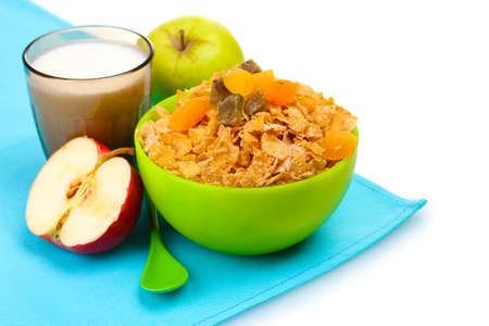 tasty cornflakes in green bowl, apples and glass of milk isolated on white photo