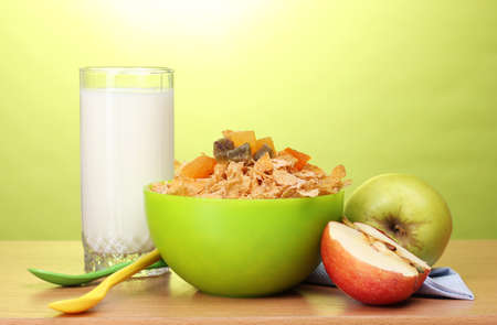 tasty cornflakes in green bowl, apples and glass of milk on wooden table on green background photo