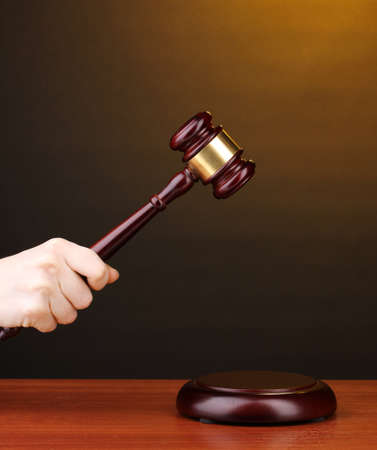 Judge's gavel in hand on brown background Stock Photo - 12265734