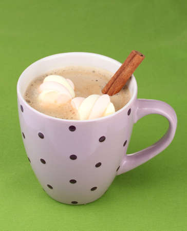 Cup of cappucino with marshmallows and cinnamon on green background photo