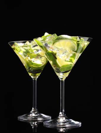 cocktails: glasses of cocktails with lime and mint on black background