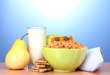 tasty cornflakes in green bowl and glass of milk on wooden table on blue background photo