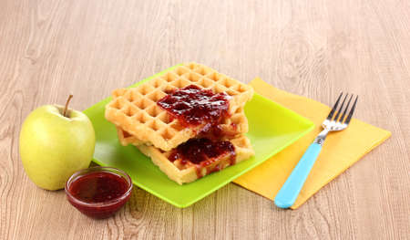 Tasty waffles with jam on plate on wooden background Stock Photo - 12247087
