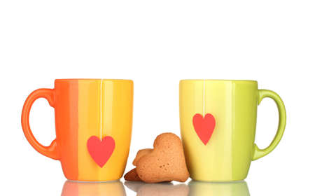 Two cups with tea bag and heart-shaped cookies isolated on white photo