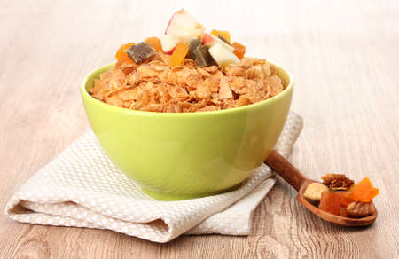 tasty cornflakes in bowl with dried fruits on wooden table photo
