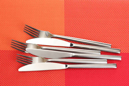 Forks and knives on a red tablecloth photo