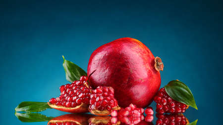 ripe pomegranate fruit with leaves on blue background photo