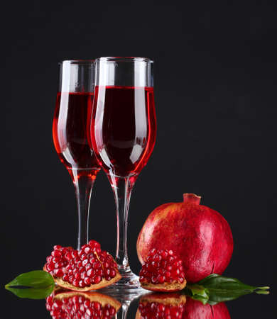 pomergranate: ripe pomergranate and glasses of wine on black background