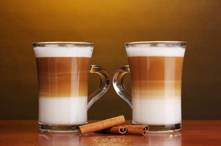 macchiato: Fragrant сoffee latte in glass cups and cinnamon on wooden table on brown background Stock Photo