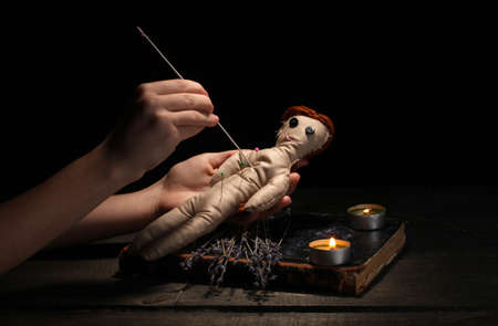 curse: Voodoo doll girl pierced by a needle on a wooden table in the candlelight