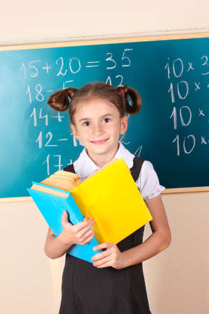 beautiful little girl with books standing near blackboard in classroom photo