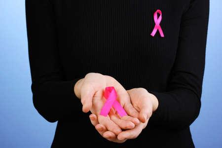 seni: Donna con nastro rosa in mano su sfondo blu