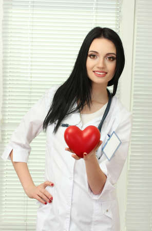 young beautiful doctor with stethoscope holding heart  Stock Photo - 12312668