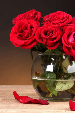 Beautiful red roses in vase on wooden table on brown background photo