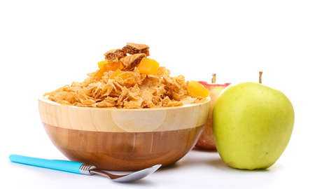 tasty cornflakes in wooden bowl and apples  isolated on white photo