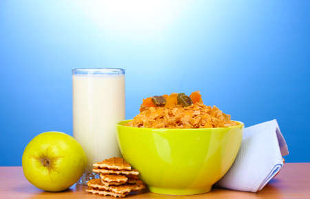 tasty cornflakes in green bowl, apples and glass of milk on wooden table on blue background Stock Photo - 12312523
