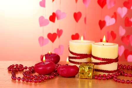 Beautiful candles with romantic decor on a wooden table on a red background Stock Photo - 12312522
