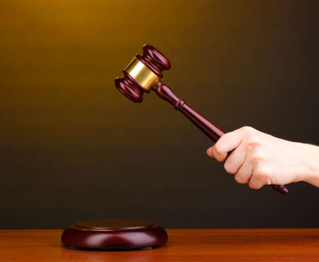 Judges gavel in hand on brown background photo