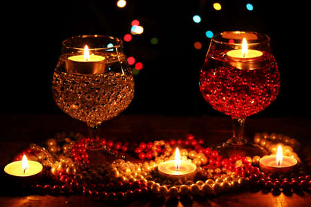 Amazing composition of candles and glasses on wooden table on bright background Stock Photo - 12312357