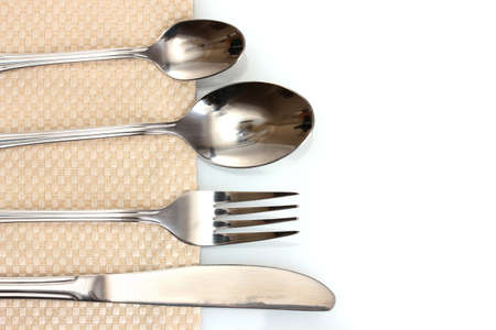 Fork, spoon and knife on a beige tablecloth Stock Photo - 12330091