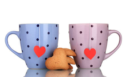 Two cups with tea bags and cookies isolated on white photo